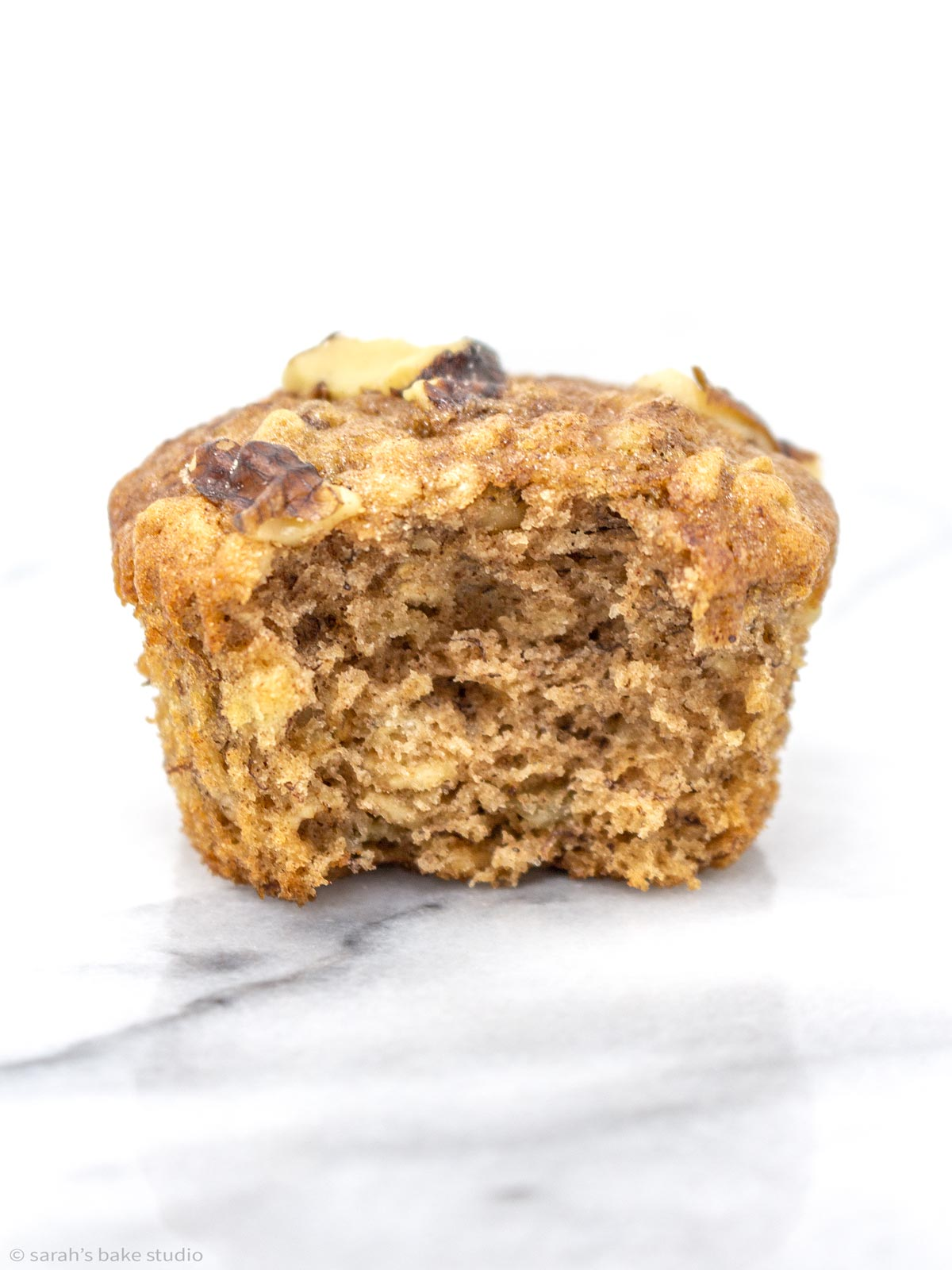 a banana walnut oatmeal muffin with a bite out of it.