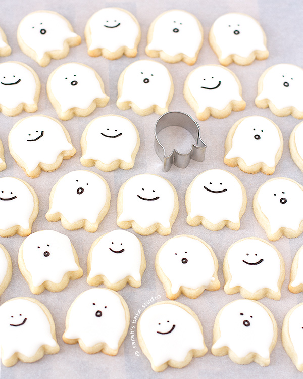 Happy Little Ghost Sugar Cookies – bite-sized, deliciously cute decorated sugar cookies that just scream sweetness with their happy little faces; you'll be in the Halloween spirit with these ghoulish cutouts!