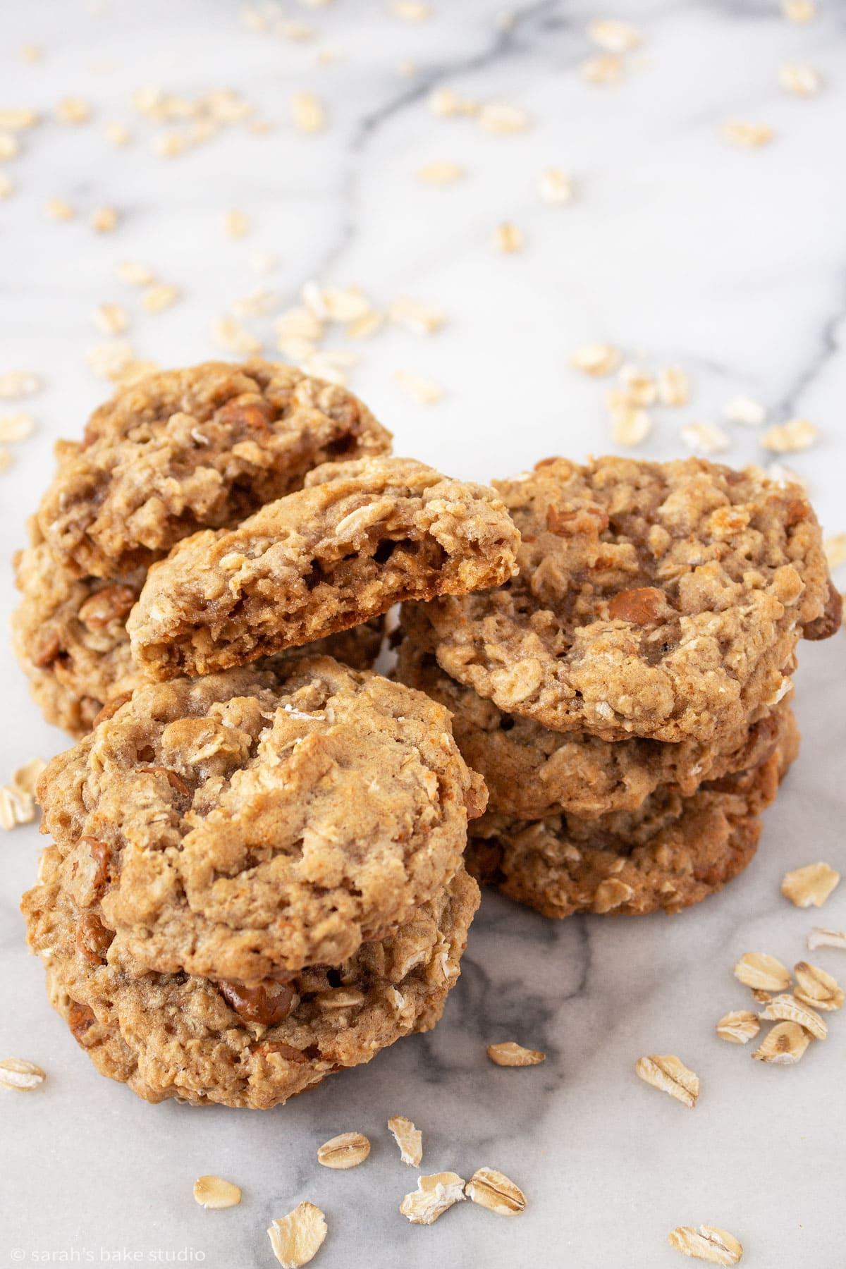 a pile of oatmeal cinnamon chip cookies with one of the cookies broken in half