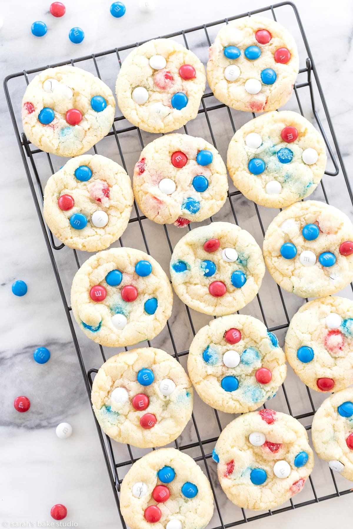 patriotic m&m cookies on a cooling rack.