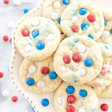 patriotic m&m cookies displayed on a white cake plate.