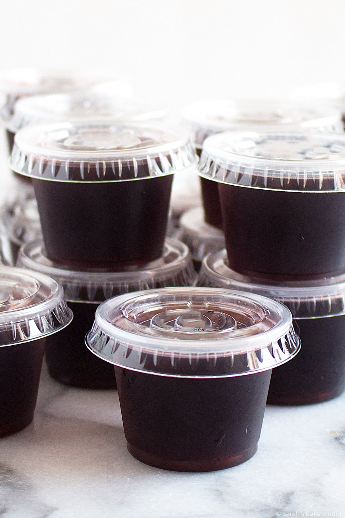 rum and coke jello shots in plastic one-ounce cups with lids
