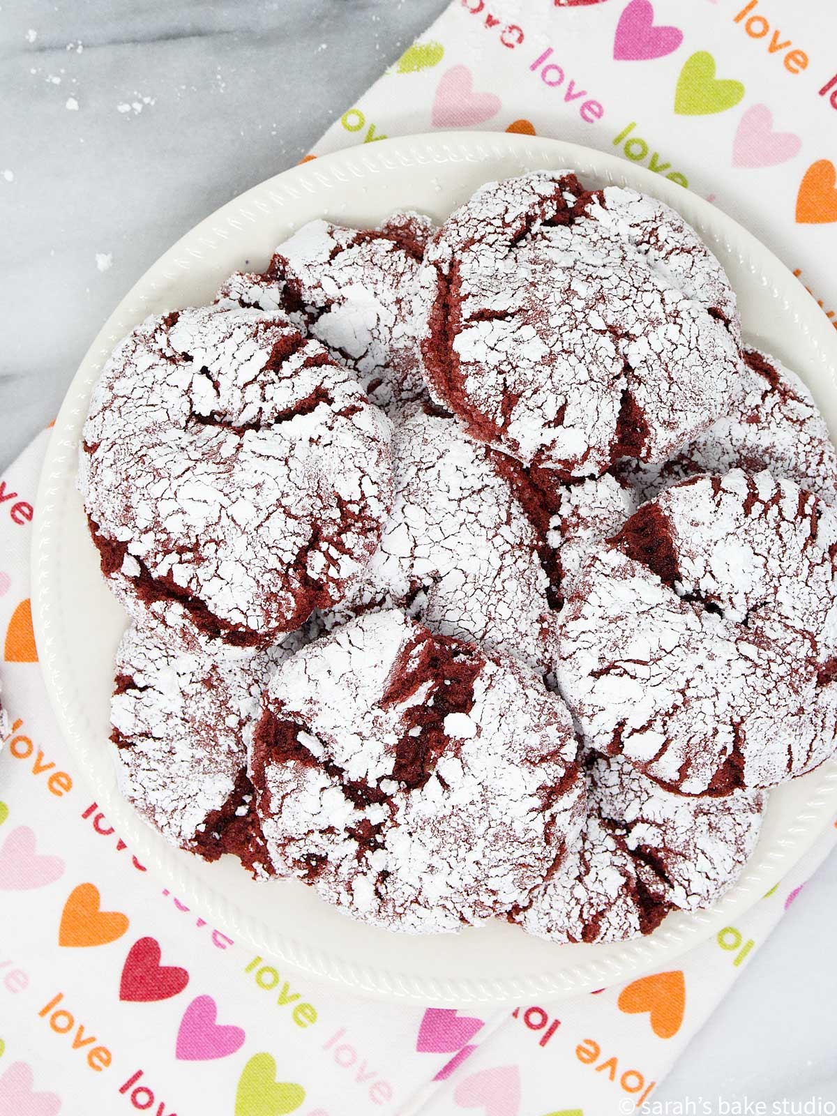red velvet crinkle cookies stacked up on plate
