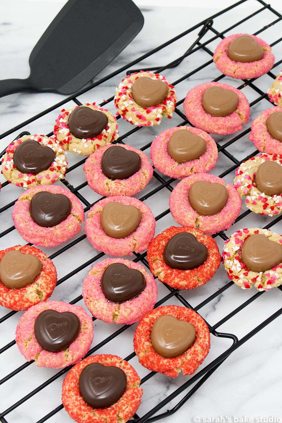 valentine peanut butter blossoms sitting on a cooling rack with a spatula next to the rack
