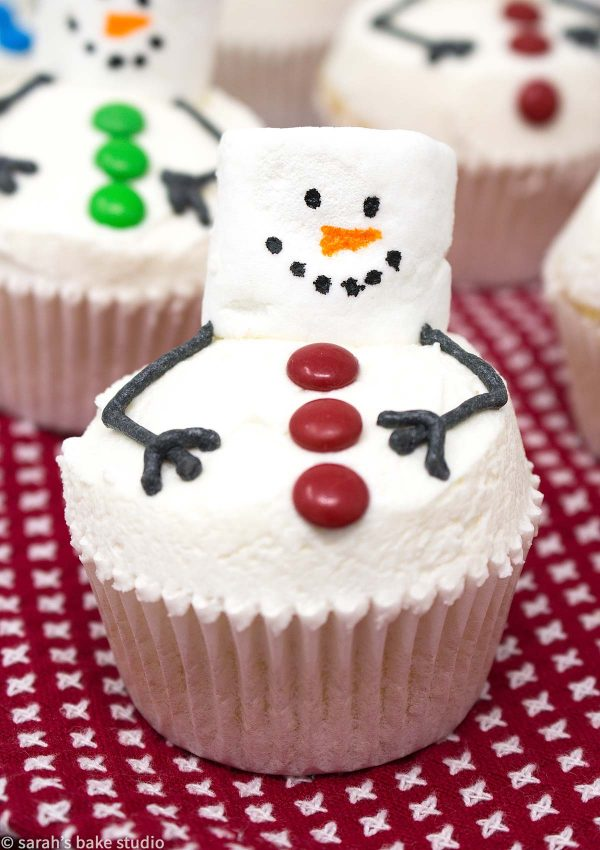 Melting Snowman Cupcakes - your favorite cupcake recipe decorated as super cute melting snowmen with marshmallows, mini M&M's candies, and vanilla buttercream; they're totes adorbs, easy enough, and all the kids (and adults) will want to eat one.