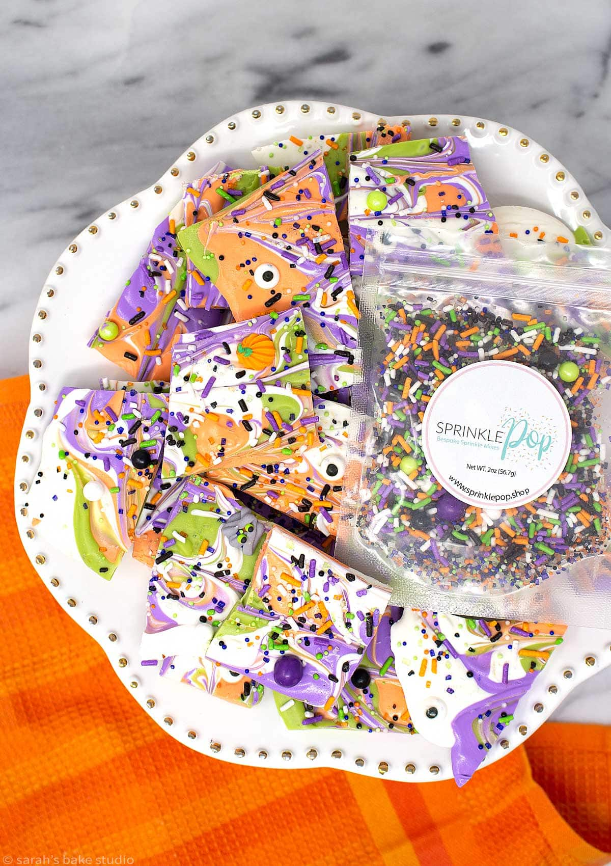 a white cake plate topped with monster mash Halloween bark and a bag of sprinkle pop sprinkles.