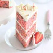 a slice of layered strawberry confetti cake on a plate.
