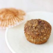 banana walnut oatmeal muffin on a white plate with the cupcake liner on the side.
