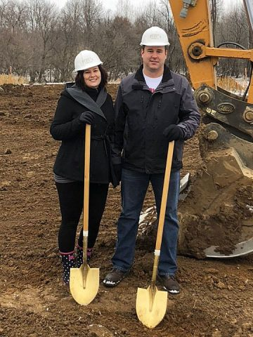 sarah and her husband with shovels breaking ground on their new home