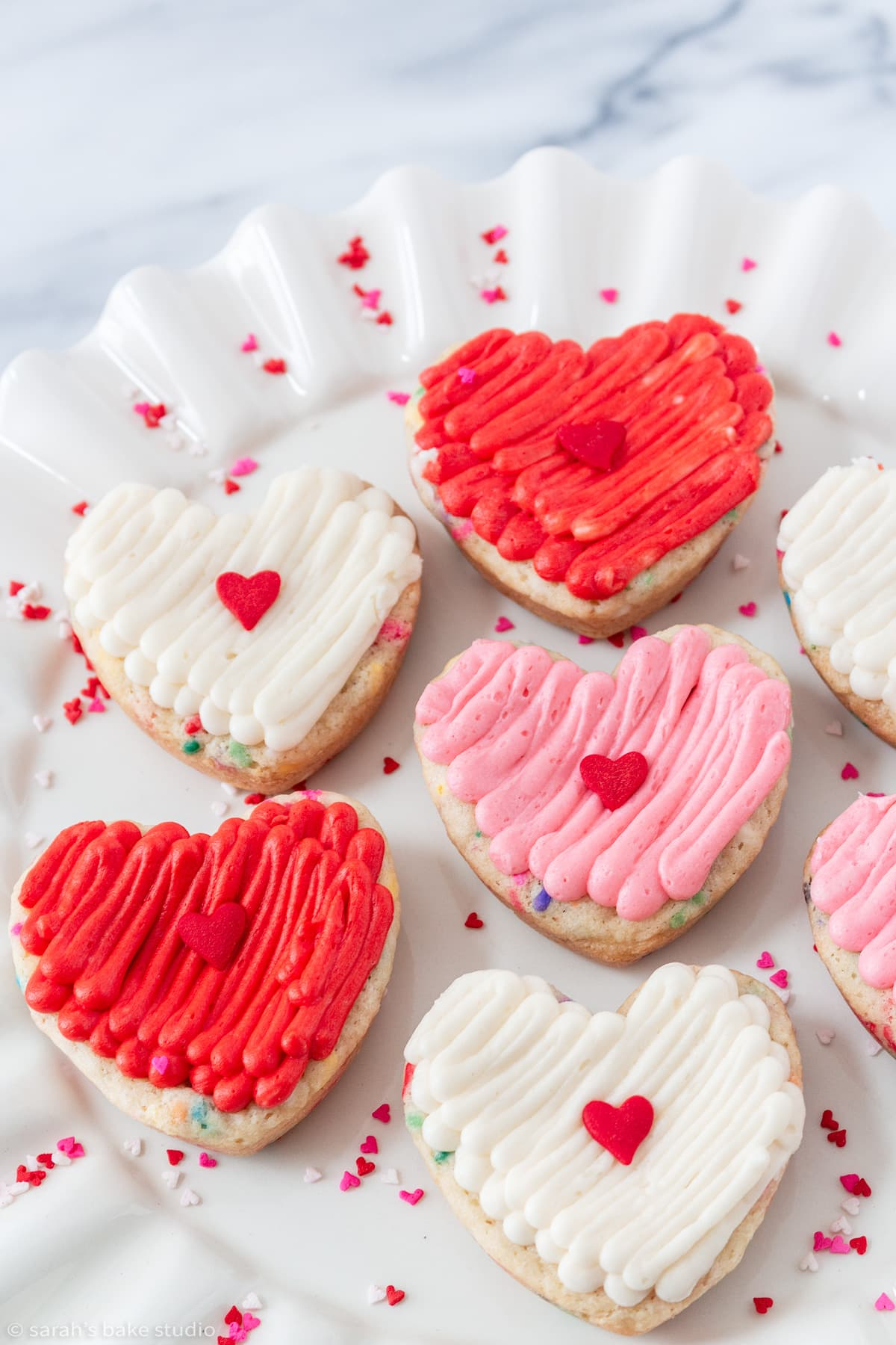 a collection of heart funfetti cookie cake bars on a plate