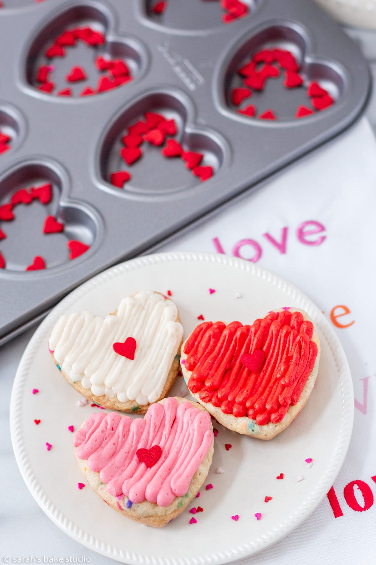 three heart funfetti cookie cake bars on a plate with the cake boss heart molded cookie pan