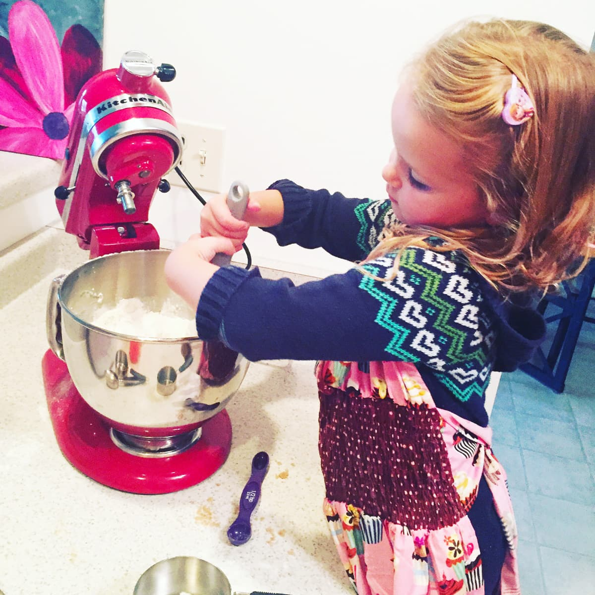 a little girl hand mixing cookie dough in a kitchenaid mixer