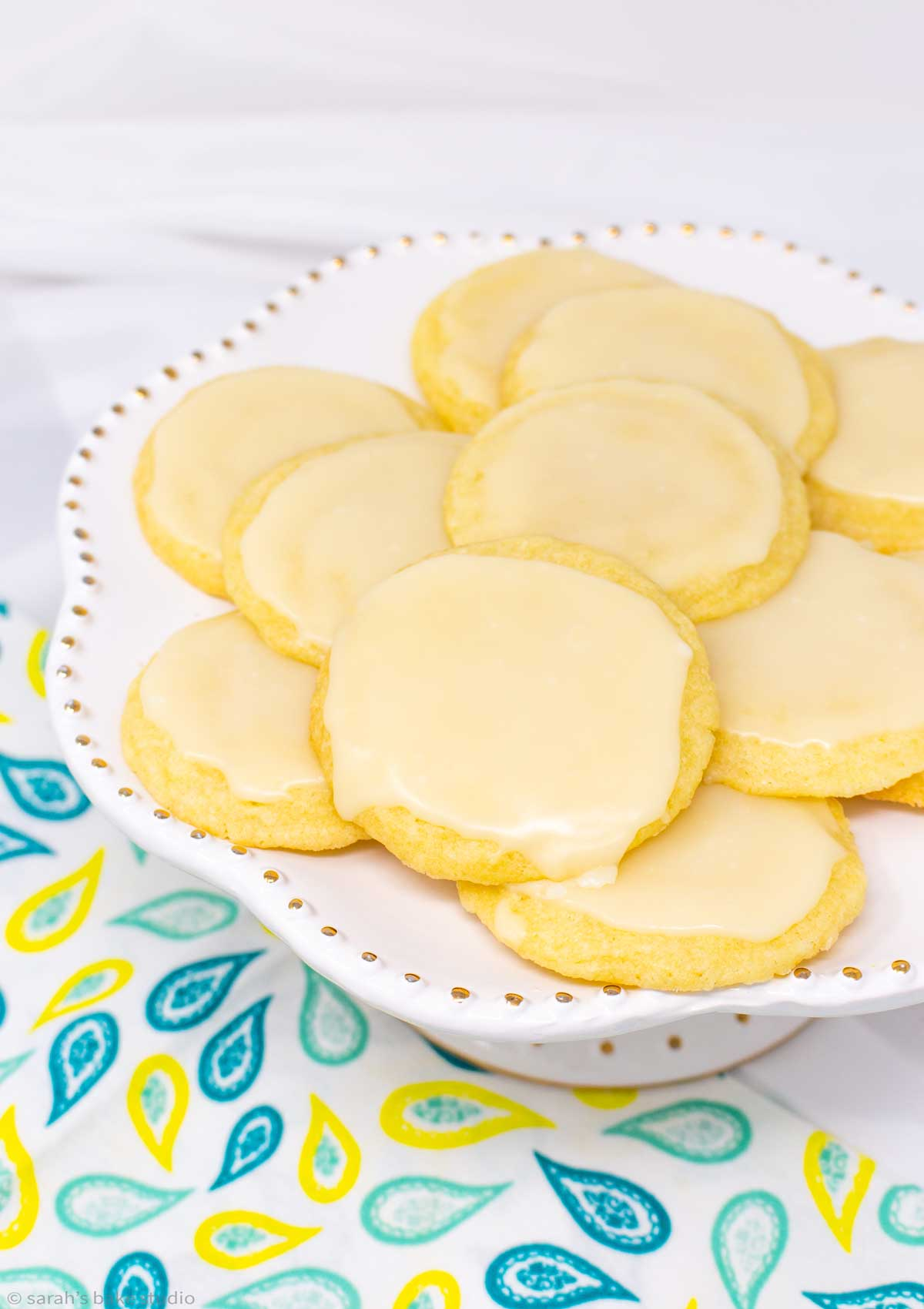 a white cake plate stacked with glazed limoncello cookies.