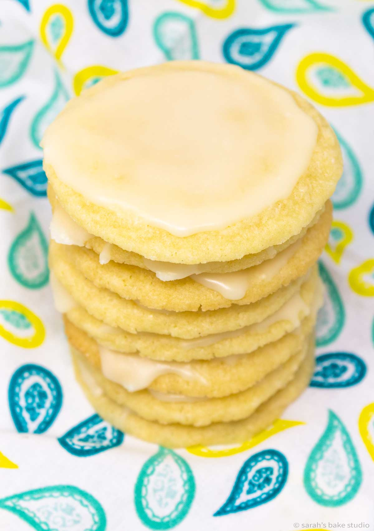 stacked glazed limoncello cookies with a view of the top of the cookies.