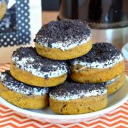 pumpkin oreo donuts stacked onto a plate.