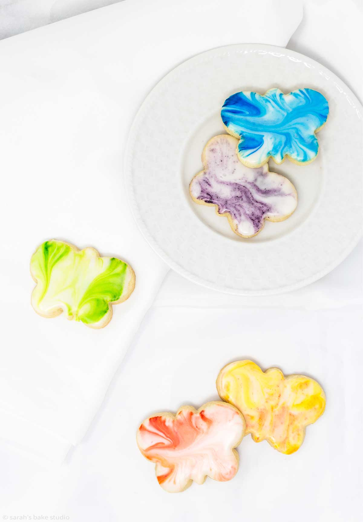 an array of marbled butterfly sugar cookies on a plate and cloth