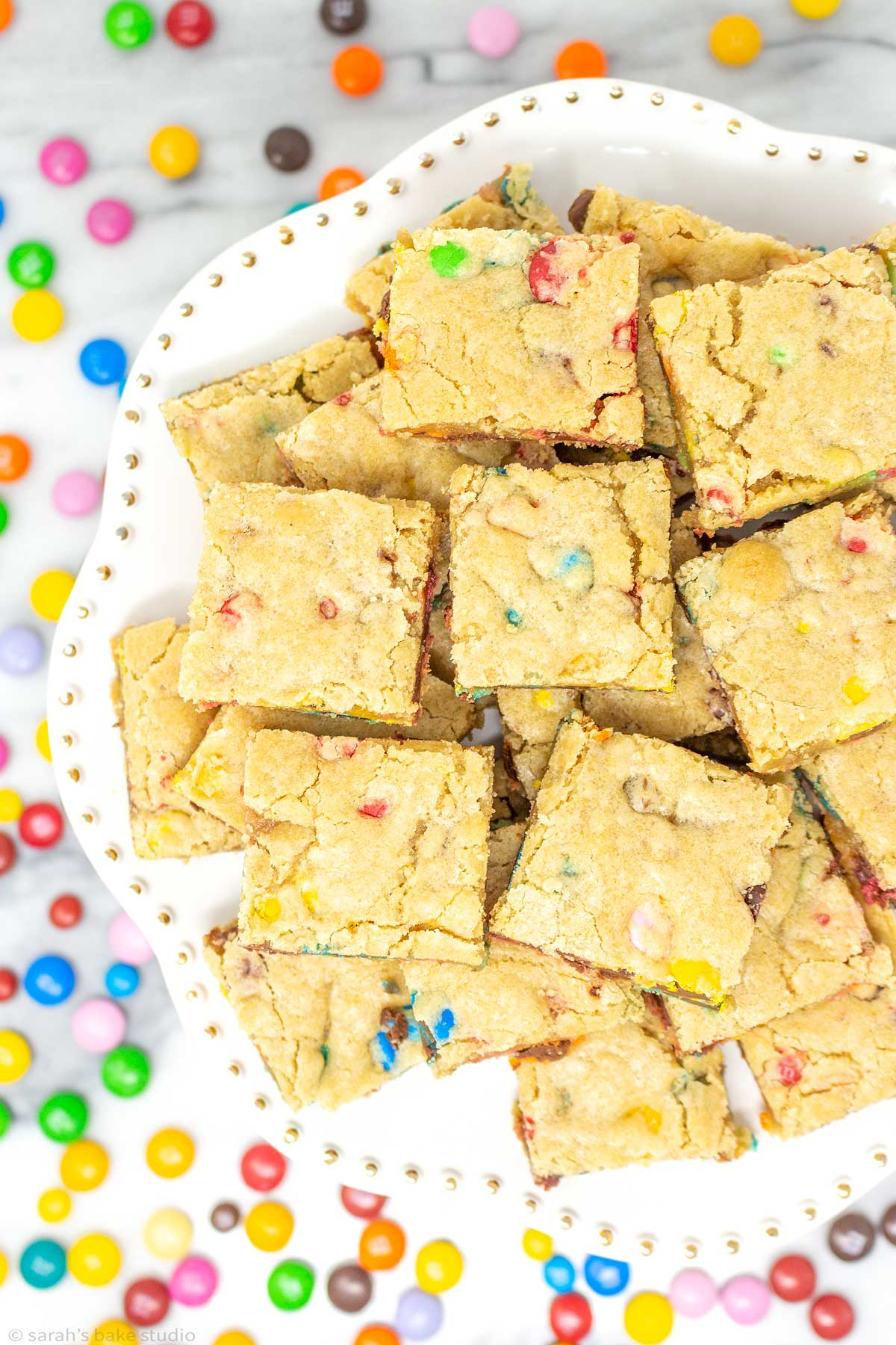 a cake plate stacked with m&m cookie bars.