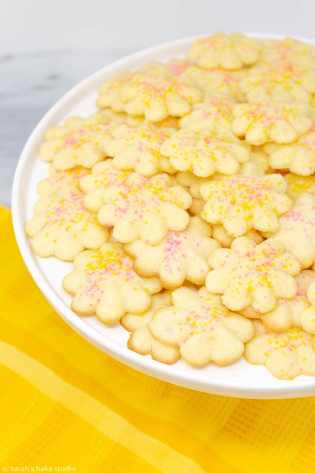 lemon spritz cookies piled onto a cake plate