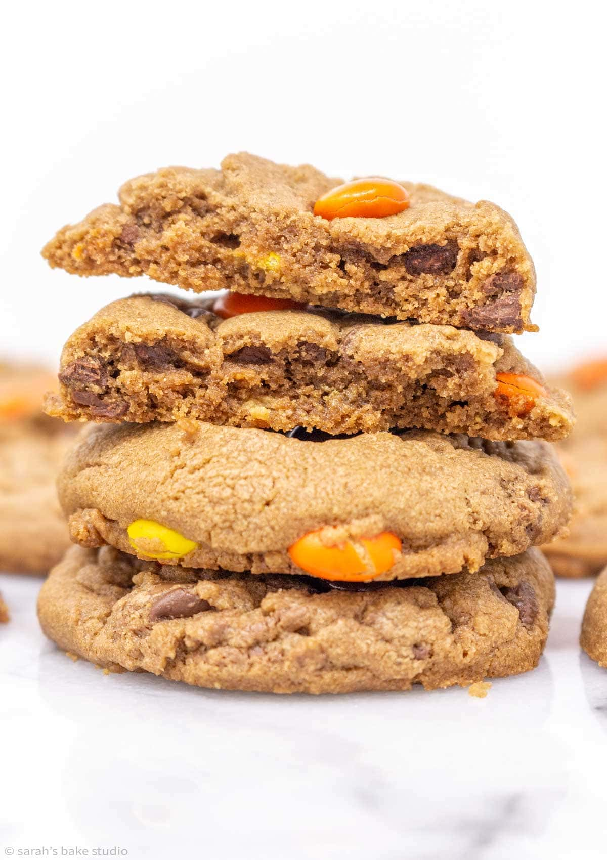 a stacked tower of Reese's chocolate peanut butter cookies with the top cookie broken in half with an inside view.