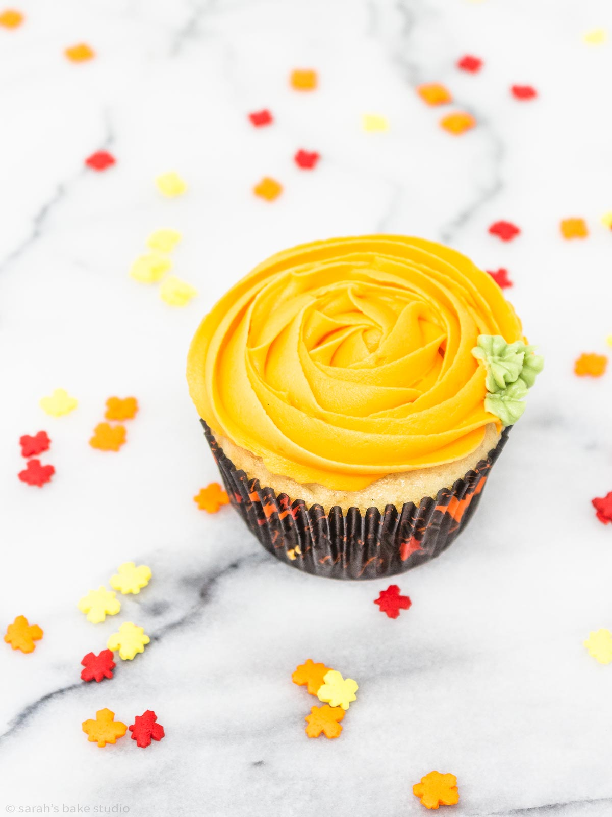 Decorated Pumpkin Cupcakes - your favorite cupcakes decorated with an orange buttercream frosting swirl, make these beautiful fall cupcakes look like they were plucked right out of the pumpkin patch.