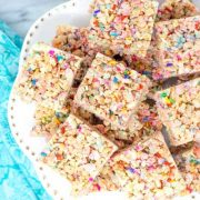 confetti rice krispies treats stacked on a white cake plate.