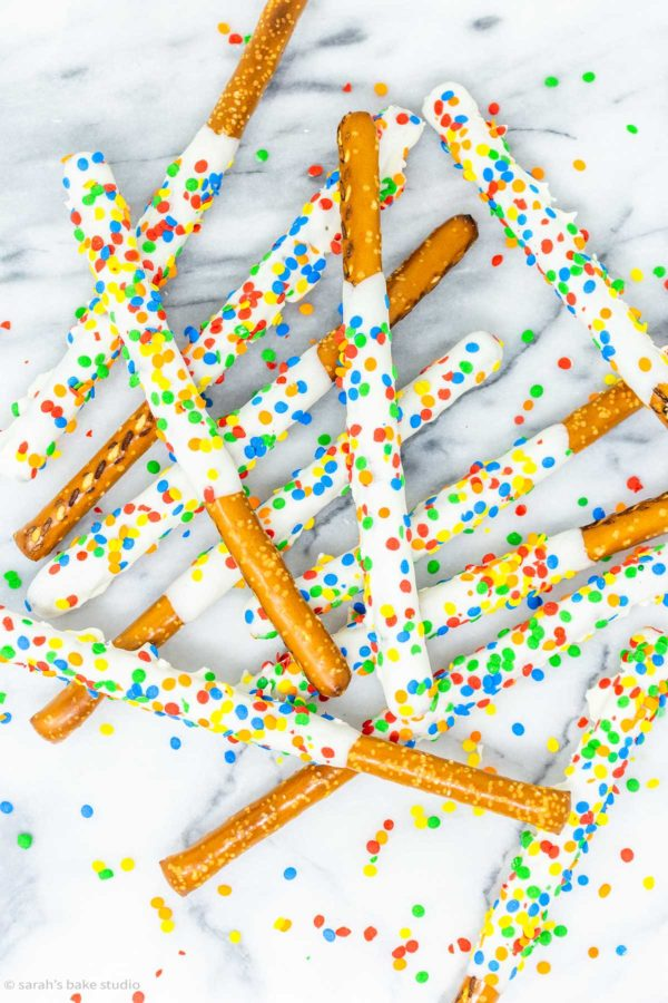 Rainbow Pretzel Wands - pretzel rods dipped in white chocolate and sprinkled with rainbow happiness; a magically delicious sweet and salty dessert.