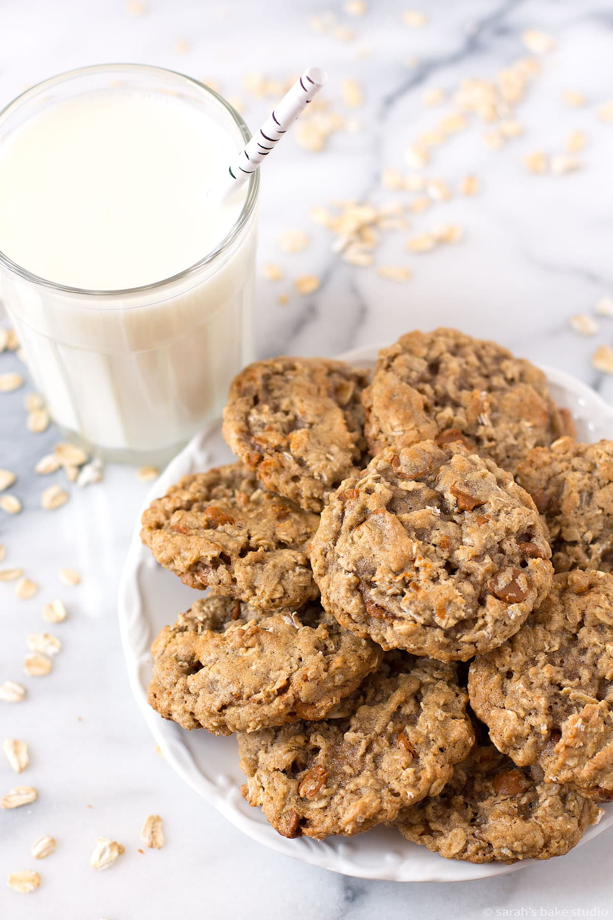 a glass of milk and a plate full of oatmeal cinnamon chip cookies